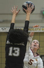 Oxnard's Robin Valtchev (13) blocks a kill attempt by Oxnard's Nicole Huelskamp in a Division 4 first-round playoff match at Oak Park  High on Thursday night. Oak Park won the match 23-25, 26-24, 25-21, 25-17.