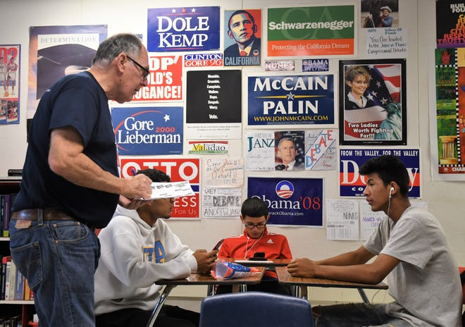 Doug Dethlefs helps Tulare Western High School students with the pre-regristration process. Behind him is a wall of political paraphernalia provided by his students over the years.