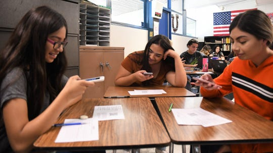 Tulare Western High School students scan QR codes to access the voter pre-registration form on their smartphones.