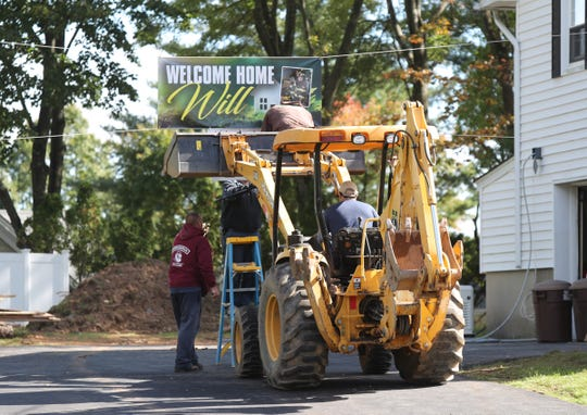 Construction workers put up a welcome home sign across the driveway of Willy McCue's home in New City on Friday, October 19, 2018.