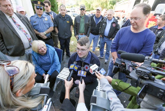 Willy McCue, Jr., 20, center, with grandmother Martha Beiber, left, and father Will McCue Sr. right, talks to the press from his New City home on Friday, October 19, 2018.