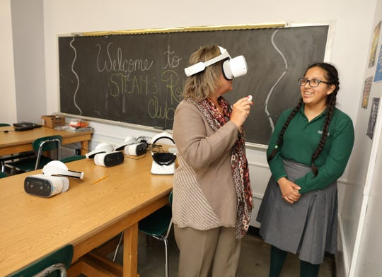 Saint Barnabas High School 9th grader Maria Romero, looks on as Fran Dziuma, the assistant principal, uses the new virtual reality goggles, Oct. 19, 2018. The equipment was obtained through an A Community Thrives grant, from the Gannett, Co.