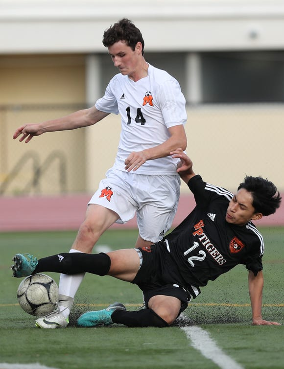 From left, Mamaroneck's Felix Miller (14) keeps the ball away from White Plains' Alan Meneses (12) during boys soccer playoff action at White Plains High School Oct. 19, 2018. Mamaroneck won the game 3-0.