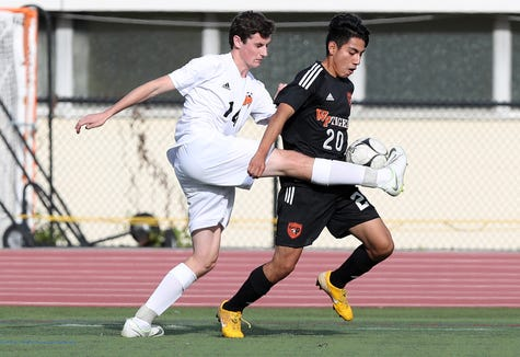 From left, Mamaroneck's Felix Miller (14) keeps the ball away from White Plains' Chris Puelles (20) during boys soccer playoff action at White Plains High School Oct. 19, 2018. Mamaroneck won the game 3-0.