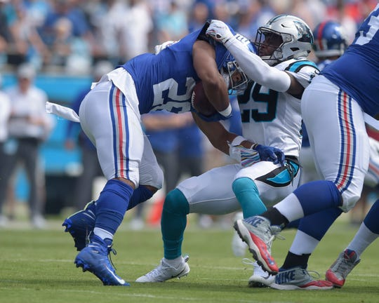 Former University of Delaware star Mike Adams brings down New York Giants' Saquon Barkley (26) in a recent game.