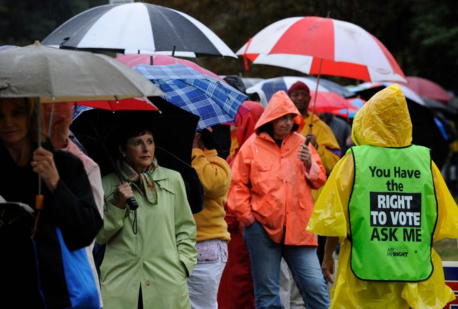 Voters stand in the rain outside Ocean View School in Norfolk, Virginia, on Nov. 4, 2008. A recent study suggests that rainy election days tend to favor Republican candidates.