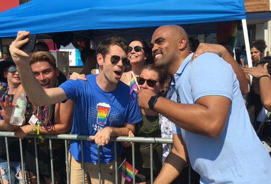 Former NFL player and Democratic congressional candidate Colin Allred, right, poses with supporters as he marches in the Dallas Pride Parade on Sept. 16, 2018 in Dallas.