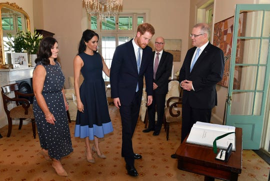 Prince Harry and Duchess Meghan of Sussex sign a visitors' book during visit with Australia's Prime Minister Scott Morrison, right, and his wife Jenny Morrison at Kirribilli House in Sydney Oct. 19, 2018. Meghan wore a sleeveless two-tone midi dress by Roxsandra with beige suede pumps.