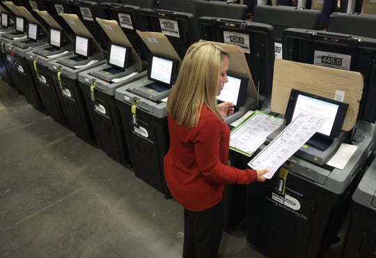 Daisy Capote, a Miami-Dade election support specialist, checks voting machines for accuracy at the Miami-Dade Election Department headquarters on Aug. 8, 2018, in Doral, Florida.