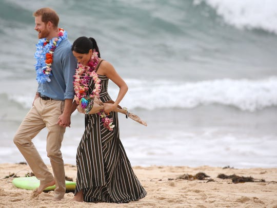 Prince Harry and Duchess Meghan of Sussex walk on famed Bondi Beach in Sydney on Oct. 19, 2018, kicking off their shoes and donning tropical garlands on Day 4 of their Down Under tour.