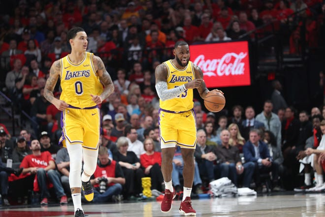 Lakers forward LeBron James shouts directions to teammates in the season opener against the Trail Blazers at Moda Center.