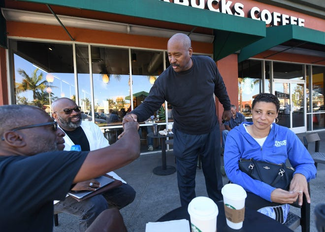 Fred Jackson, left, greets a friend in front of the Ladera Starbucks. The friends with Greg Medger Parrish, center, and Rosemary William have been gathering at that Starbucks since its opening in 1998.