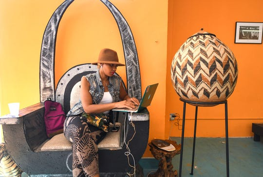 Jherimi Harmoni works on her laptop in Hot & Cool Cafe. The business is filled with art on the walls and Afrocentric furniture.