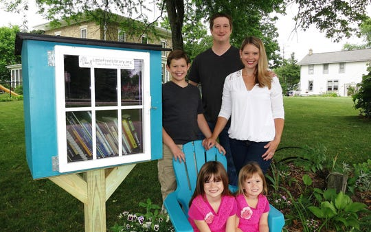 The Nelson family poses by the Little Free Library in front of their home in Pewaukee, Wisconsin. Standing are Benjamin Nelson, 10, and parents Paul Nelson and Heather Nelson. Seated are Alayna Nelson, 6, left, and Kennady Nelson, 3.