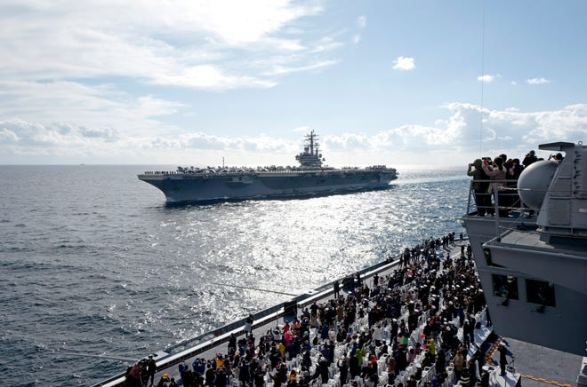 Spectators watch the US Navy's Nimitz-class aircraft carrier USS Ronald Reagan sailing during the International Fleet Review in the sea of Seogwipo, off the island of Jeju, South Korea, 11 October 2018.