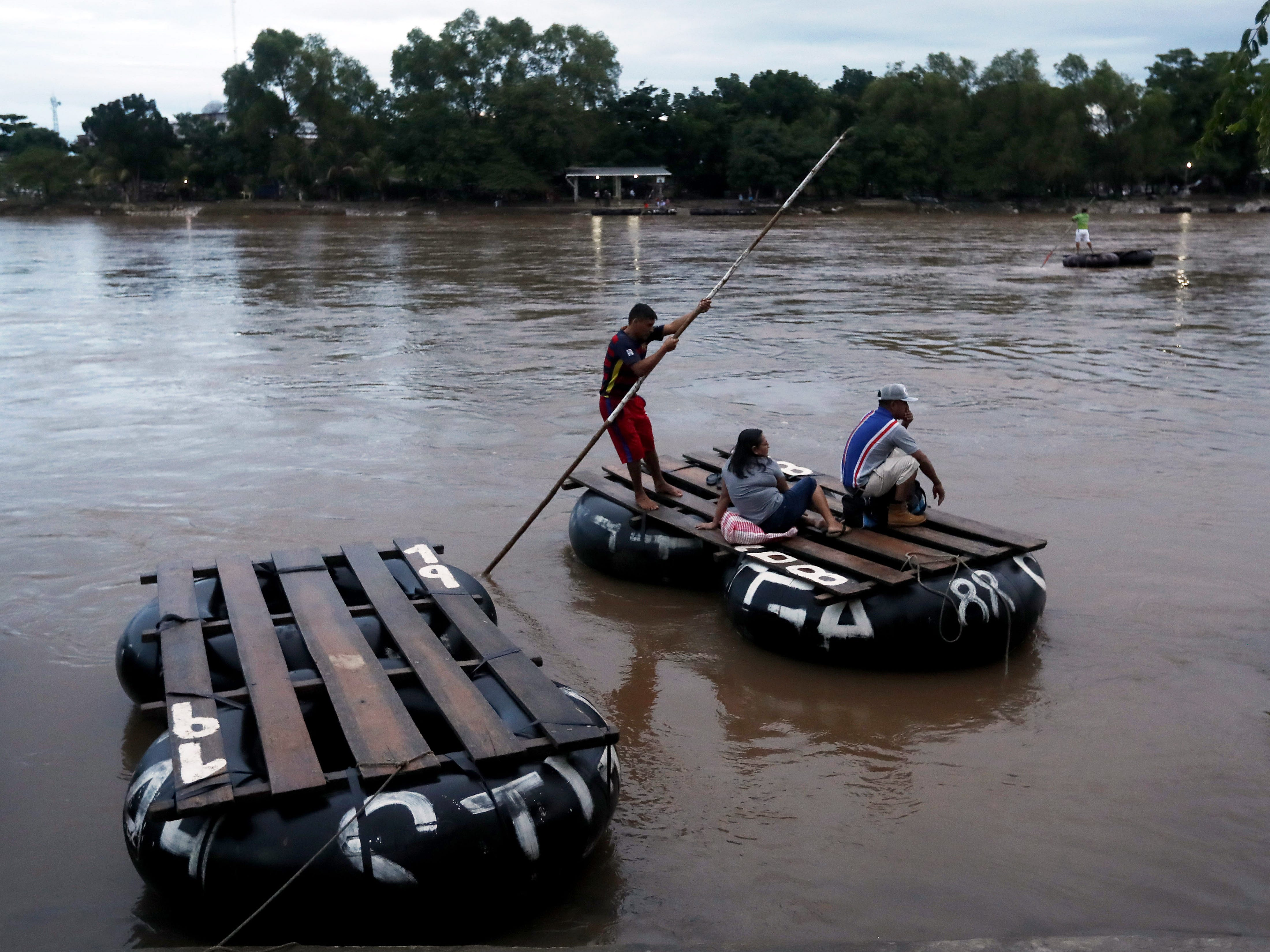 epa07104768 Rafters help Honduran migrants to cross the Suchiate River that divides Guatemala and Mexico in Escuintla, Guatemala, on 19 October 2018, from where they will continue their journey to USA.  EPA-EFE/ESTEBAN BIBA ORG XMIT: GU502