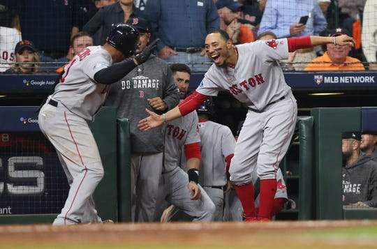 ALCS Game 5: Red Sox third baseman Rafael Devers celebrates with outfielder Mookie Betts after hitting a three-run home run in the sixth inning.