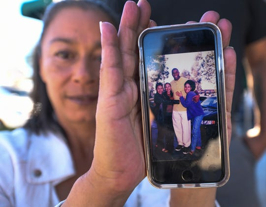 "Toney Carson holds up a snapshot on her cellphone of her and other locals who  gathered as a Starbucks in Ladera with former Lakers star Earvin ""Magic"" Johnson when it opened in 1998."