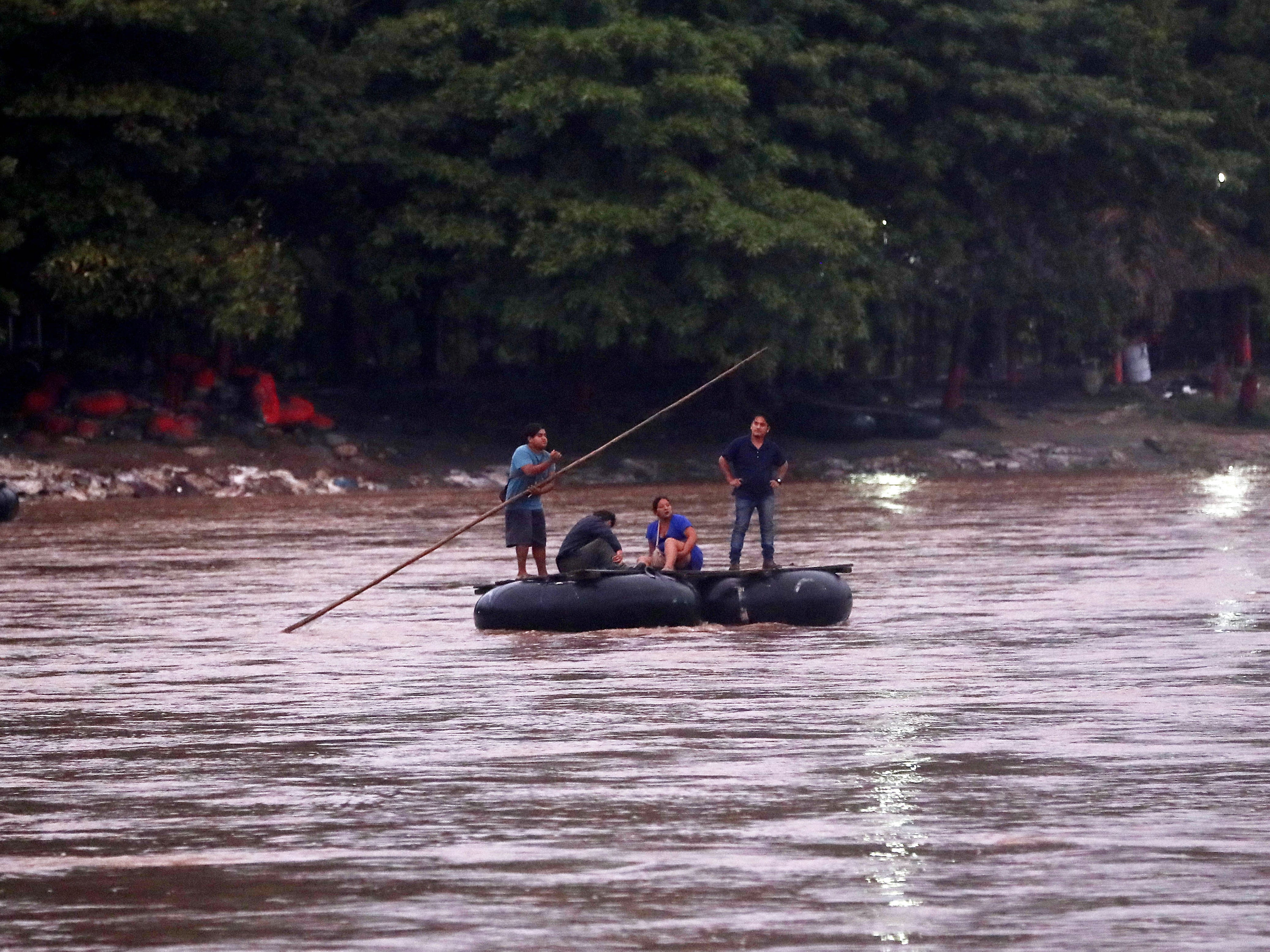 epa07104770 Rafters help Honduran migrants to cross the Suchiate River that divides Guatemala and Mexico in Escuintla, Guatemala, on 19 October 2018, from where they will continue their journey to USA.  EPA-EFE/ESTEBAN BIBA ORG XMIT: GU502