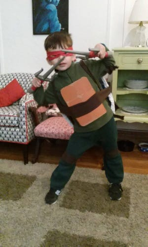 Jude Herron dressed in a homemade Teenage Mutant Ninja Turtle costume in 2014. The project cost $11.