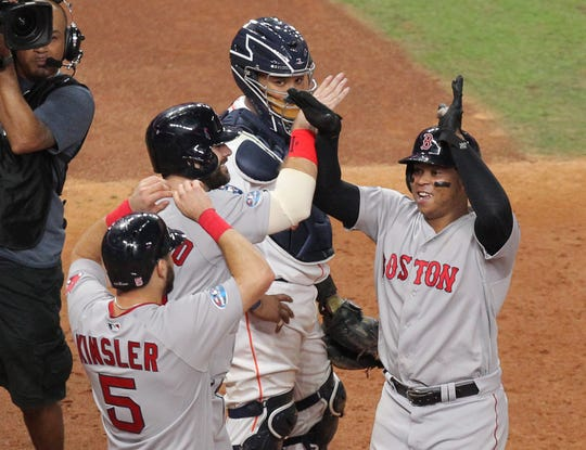 Rafael Devers (right) celebrates withIan Kinsler and Mitch Moreland after hitting a three-run home run in the sixth inning.