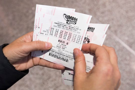 A woman holds Mega Millions lottery tickets she just bought from a machine in Washington, D.C. on October 18, 2018. Mega Millions, a 44-state lottery, has a record jackpot of nearly one billion.