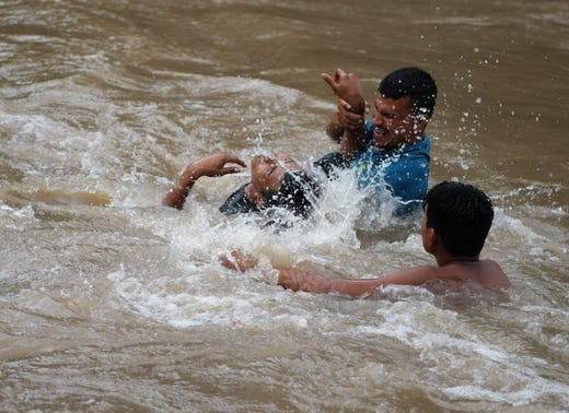 """TOPSHOT - Honduran migrants attempt to cross the border Goascoran River to enter illegally to El Salvador, in Goascoran, Honduras on October 18, 2018. - US President Donald Trump threatened Thursday to send the military to close its southern border if Mexico fails to stem the """"onslaught"""" of migrants from Central America, in a series of tweets that blamed Democrats ahead of the midterm elections. (Photo by MARVIN RECINOS / AFP)MARVIN RECINOS/AFP/Getty Images ORG XMIT: 207 ORIG FILE ID: AFP_1A477L"""