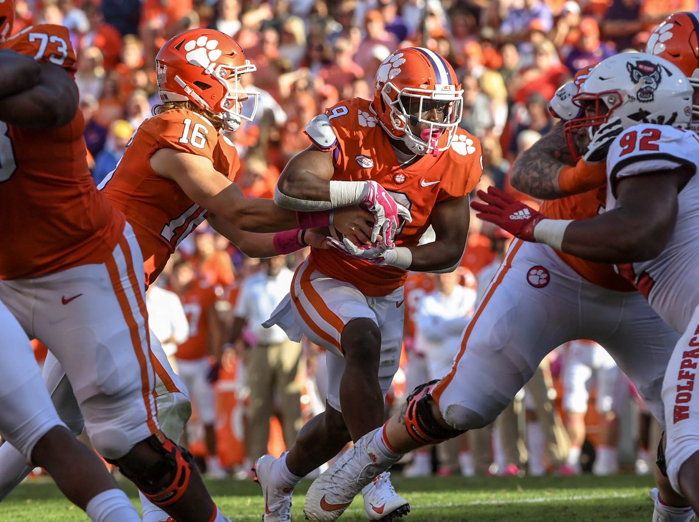 Clemson quarterback Trevor Lawrence (16) hands off to running back Travis Etienne (9) near NC State defensive tackle Larrell Murchison (92) during the second quarter in Memorial Stadium on Saturday, October 20, 2018.