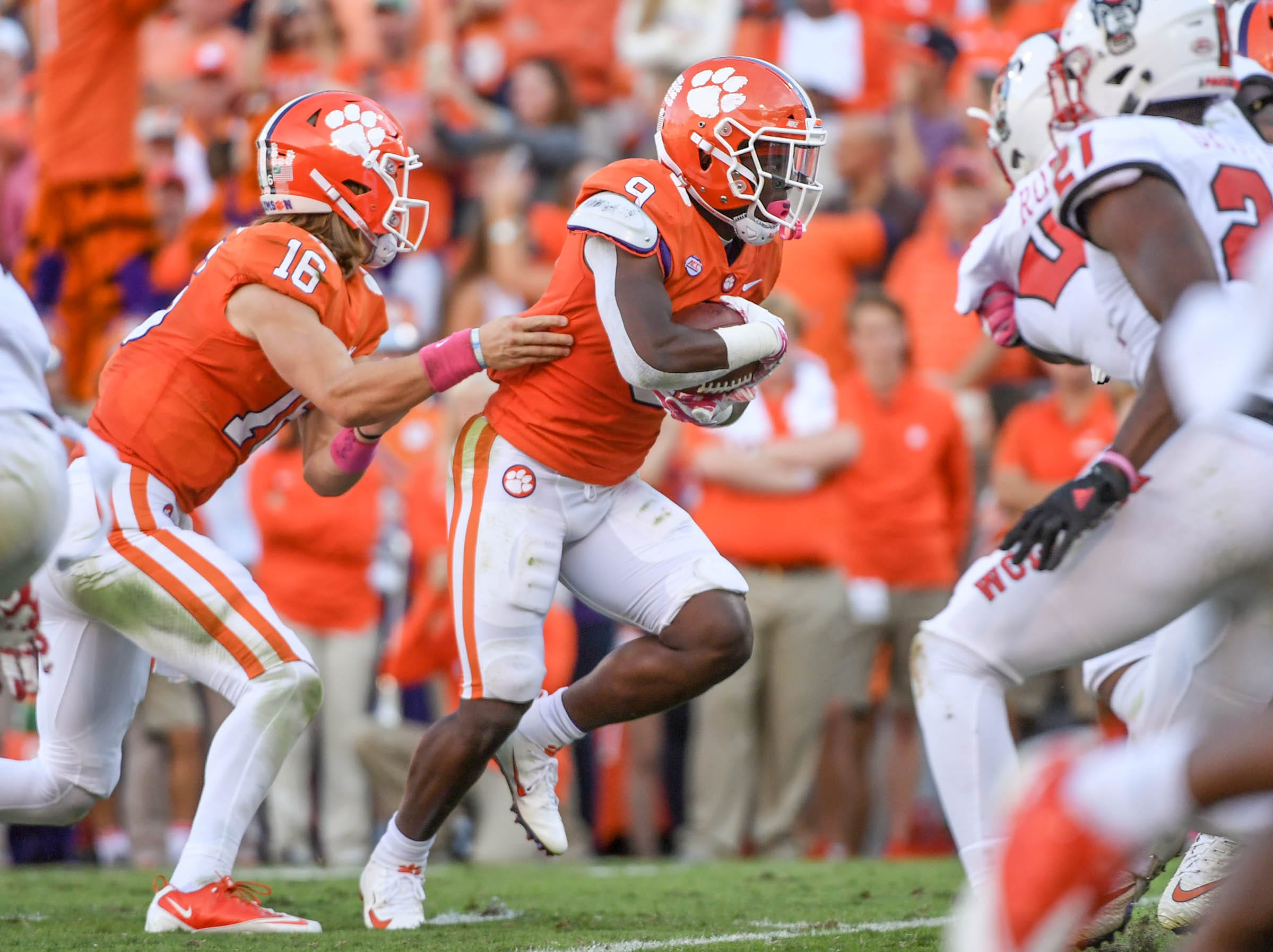 Clemson quarterback Trevor Lawrence (16) hands off to running back Travis Etienne (9) on his way to scoring a touchdown during the second quarter in Memorial Stadium on Saturday, October 20, 2018.