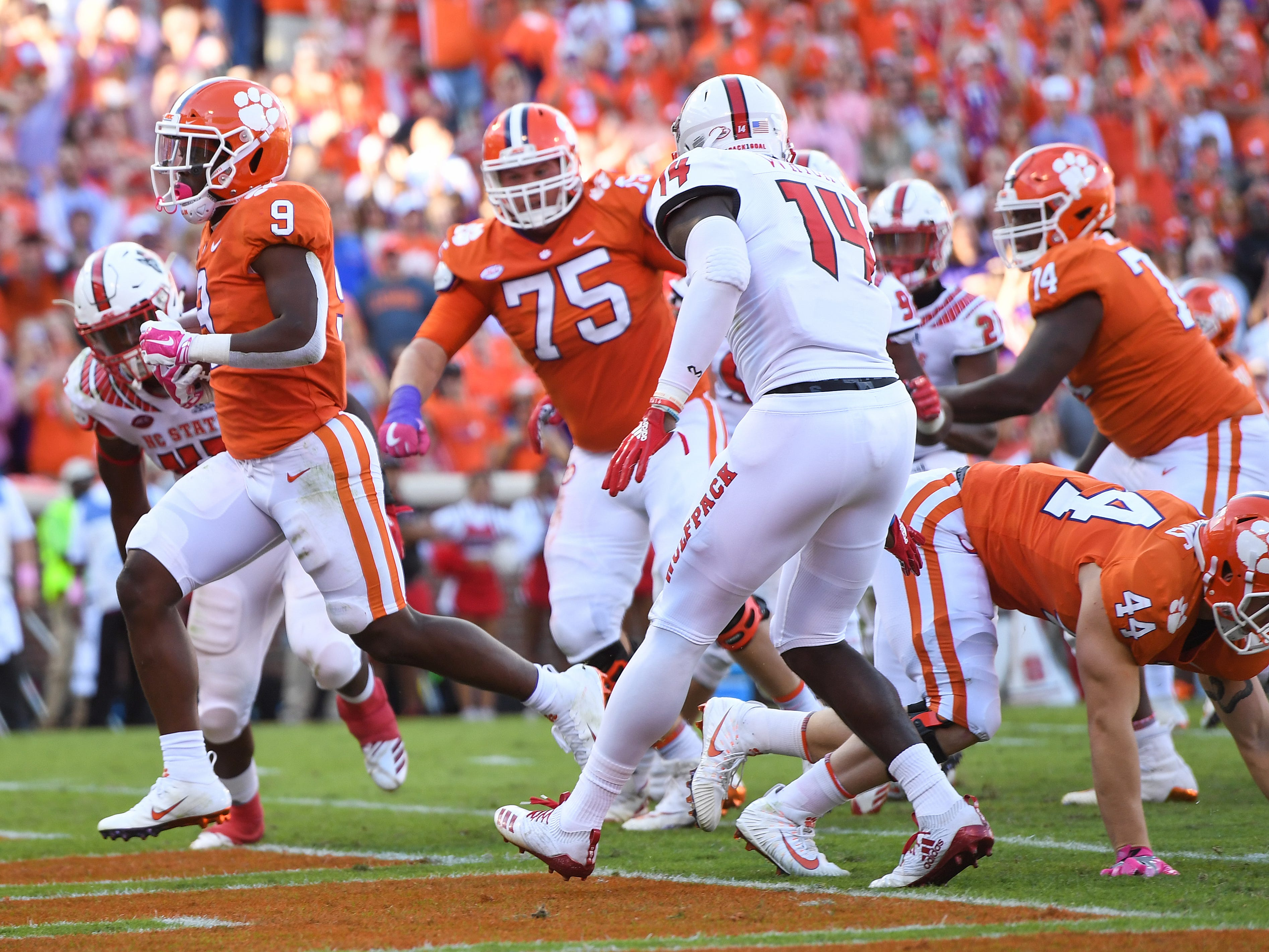 Clemson running back Travis Etienne (9) scores against NC State during the second quarter.