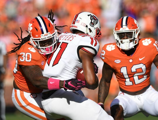 Clemson linebacker Jalen Williams (30) brings down NC State wide receiver Jakobi Meyers (11) Saturday at Clemson's Memorial Stadium.