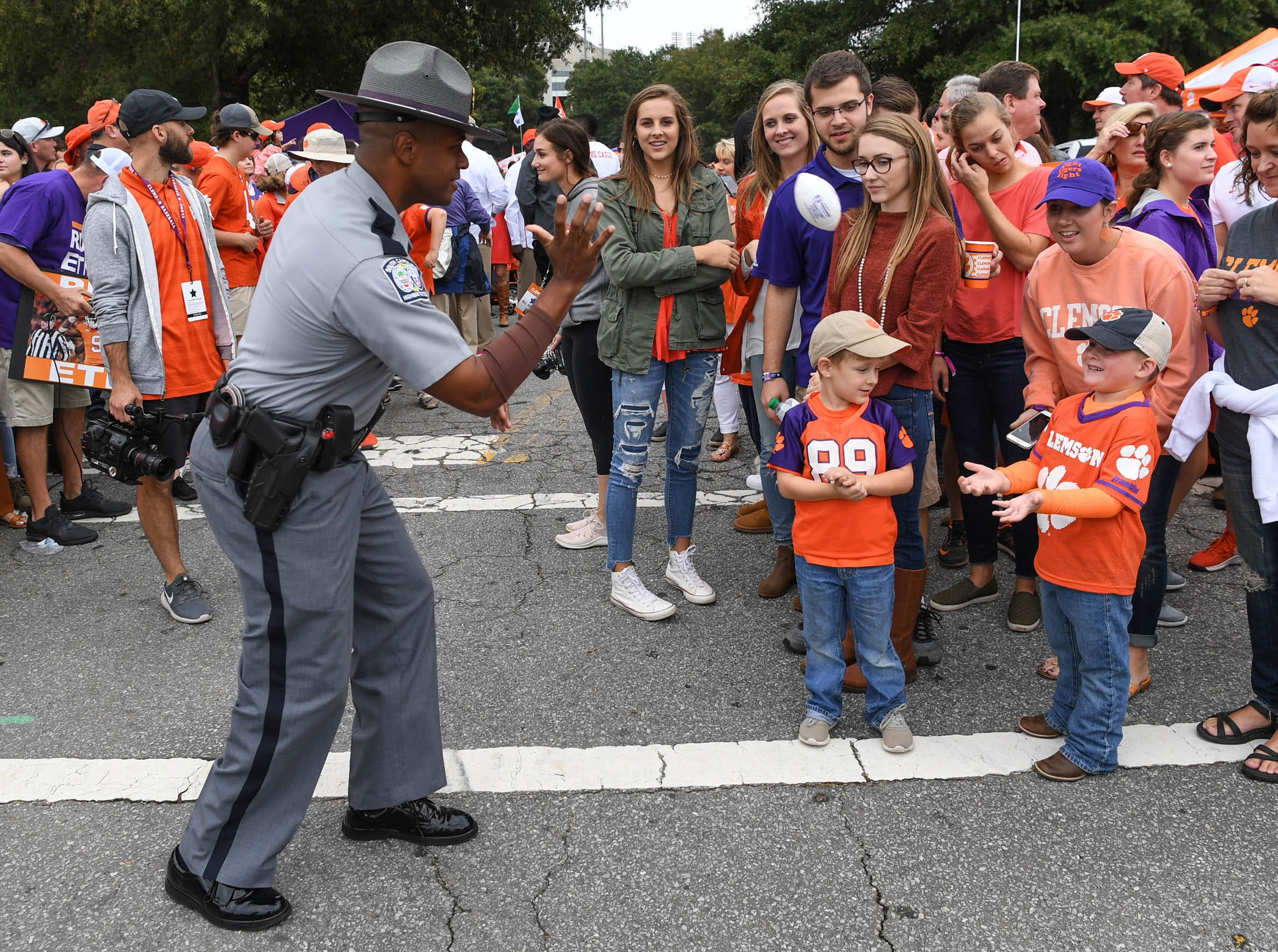 South Carolina Trooper J.W. Price tosses a plastic football with Garner Wash of Saluda minutes before Tiger Walk before the game in Memorial Stadium on Saturday, October 20, 2018.