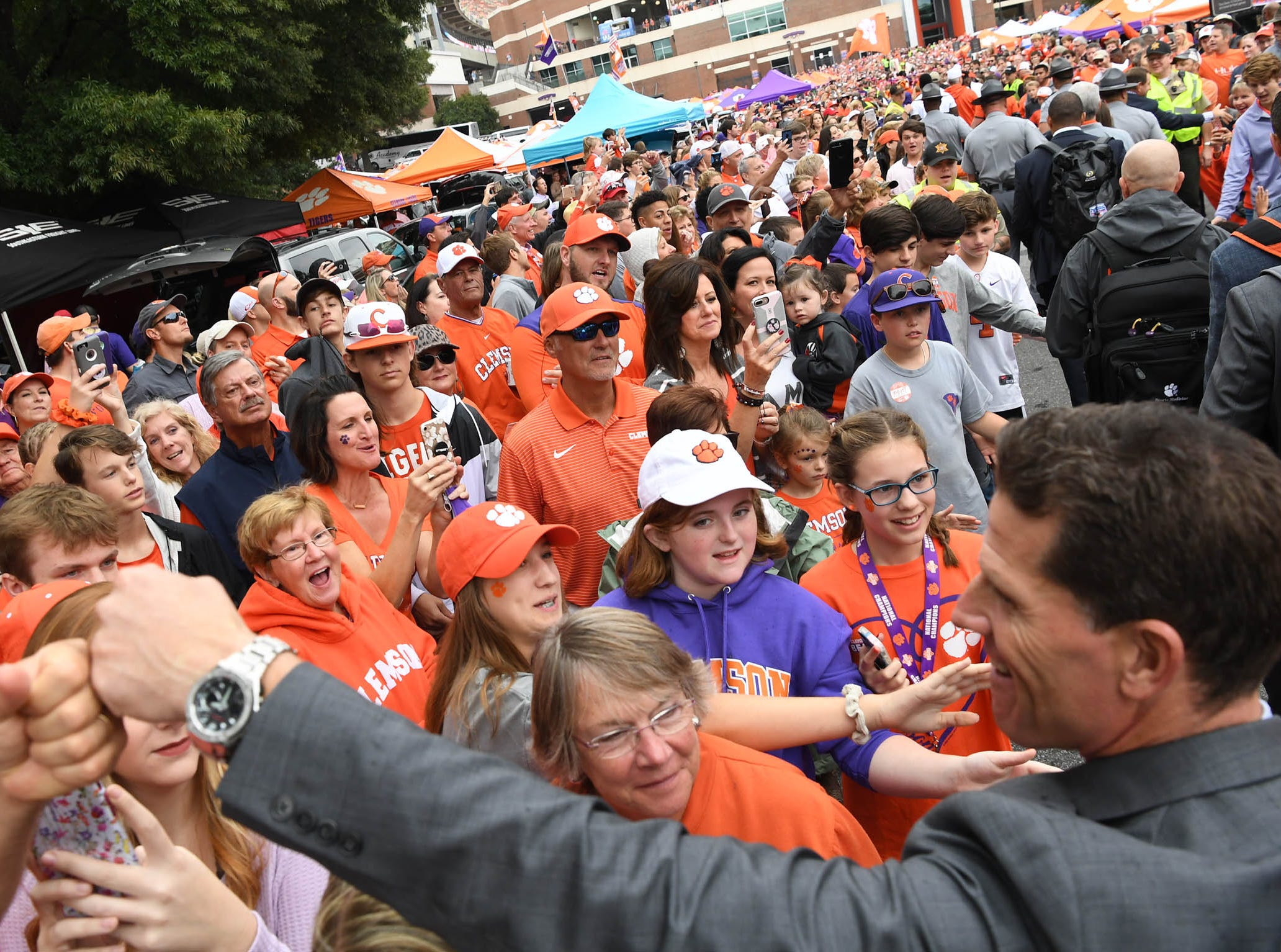 Clemson Defensive Coordinator Brent Venables walks by cheering fans during Tiger Walk before the game in Memorial Stadium on Saturday, October 20, 2018.