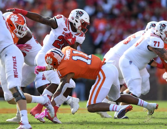Clemson safety Isaiah Simmons (11) stops N.C. State running back Ricky Person Jr. (20) during the first quarter Saturday.