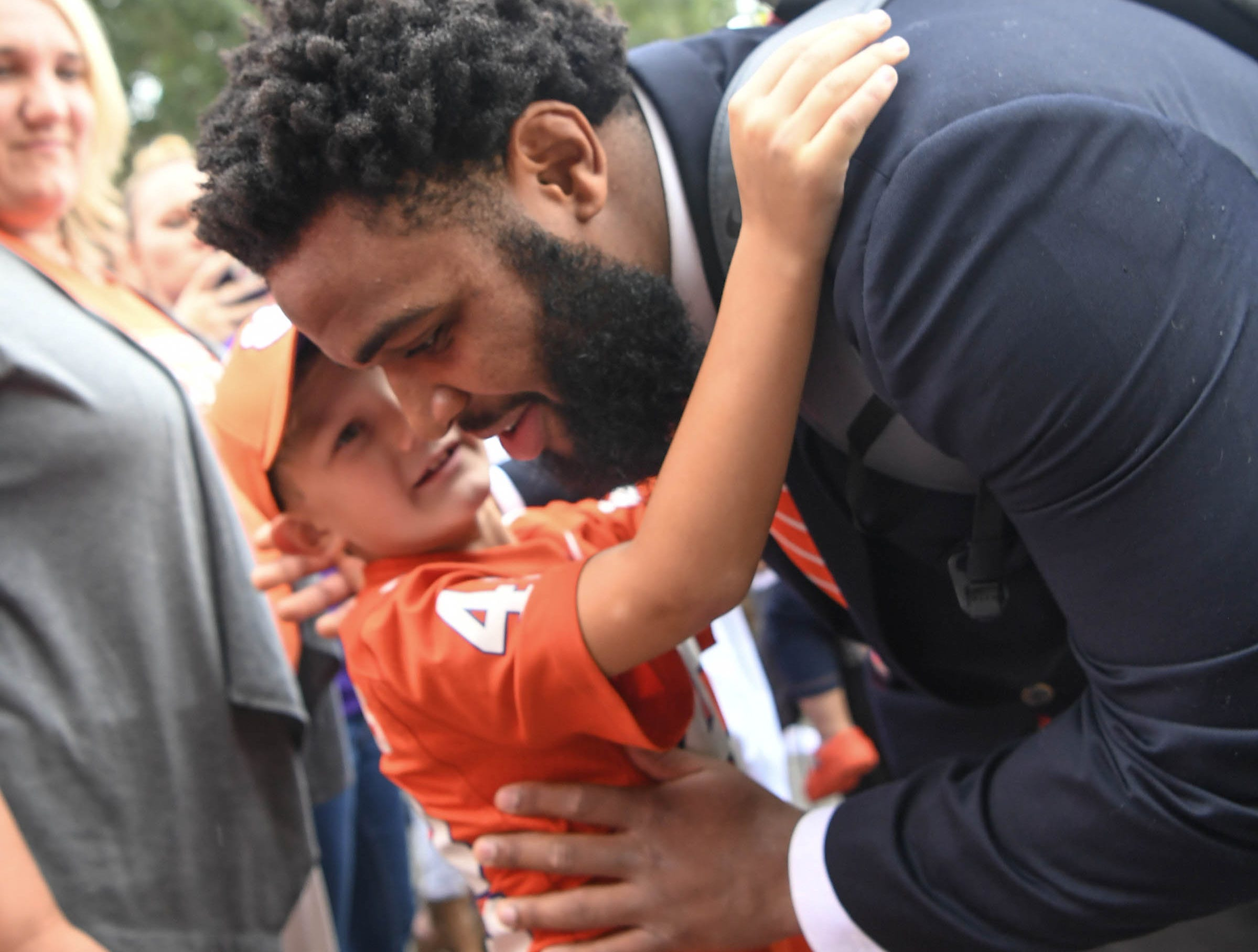 Clemson defensive lineman Christian Wilkins stops to hug a young fan during Tiger Walk before the game in Memorial Stadium on Saturday, October 20, 2018.