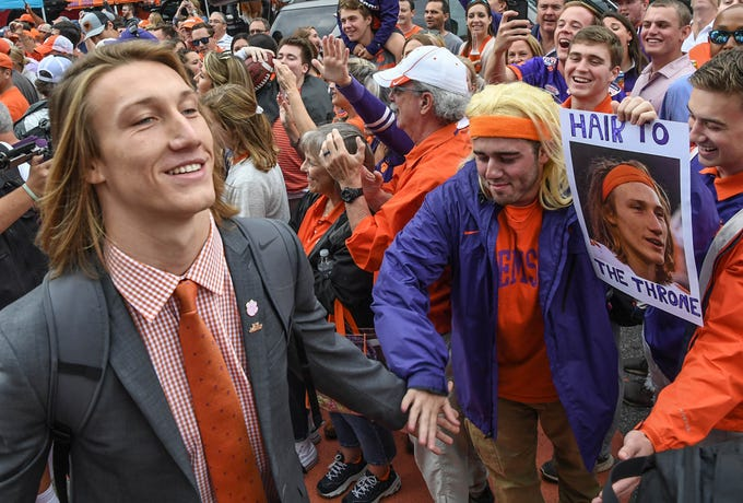 Clemson quarterback Trevor Lawrence, left, walks by a fan holding a sign for him during Tiger Walk before the game in Memorial Stadium on Saturday, October 20, 2018.