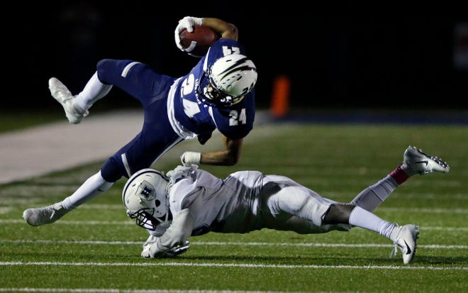 Ian Laatsch of Appleton North is tackled by Jakes Asembo of Hudson in a WIAA Division 1 football playoff game Friday at Paul Engen Field in Appleton.