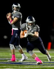 Menasha's Tyler Roehl, 22, runs against Hortonville at Calder Stadium in Menasha last season.