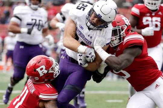 Northwestern running back Isaiah Bowser, center, is tackled by Rutgers defensive back Isaiah Wharton, left, and linebacker Trevor Morris during the first half of an NCAA college football game, Saturday, Oct. 20, 2018, in Piscataway, N.J.