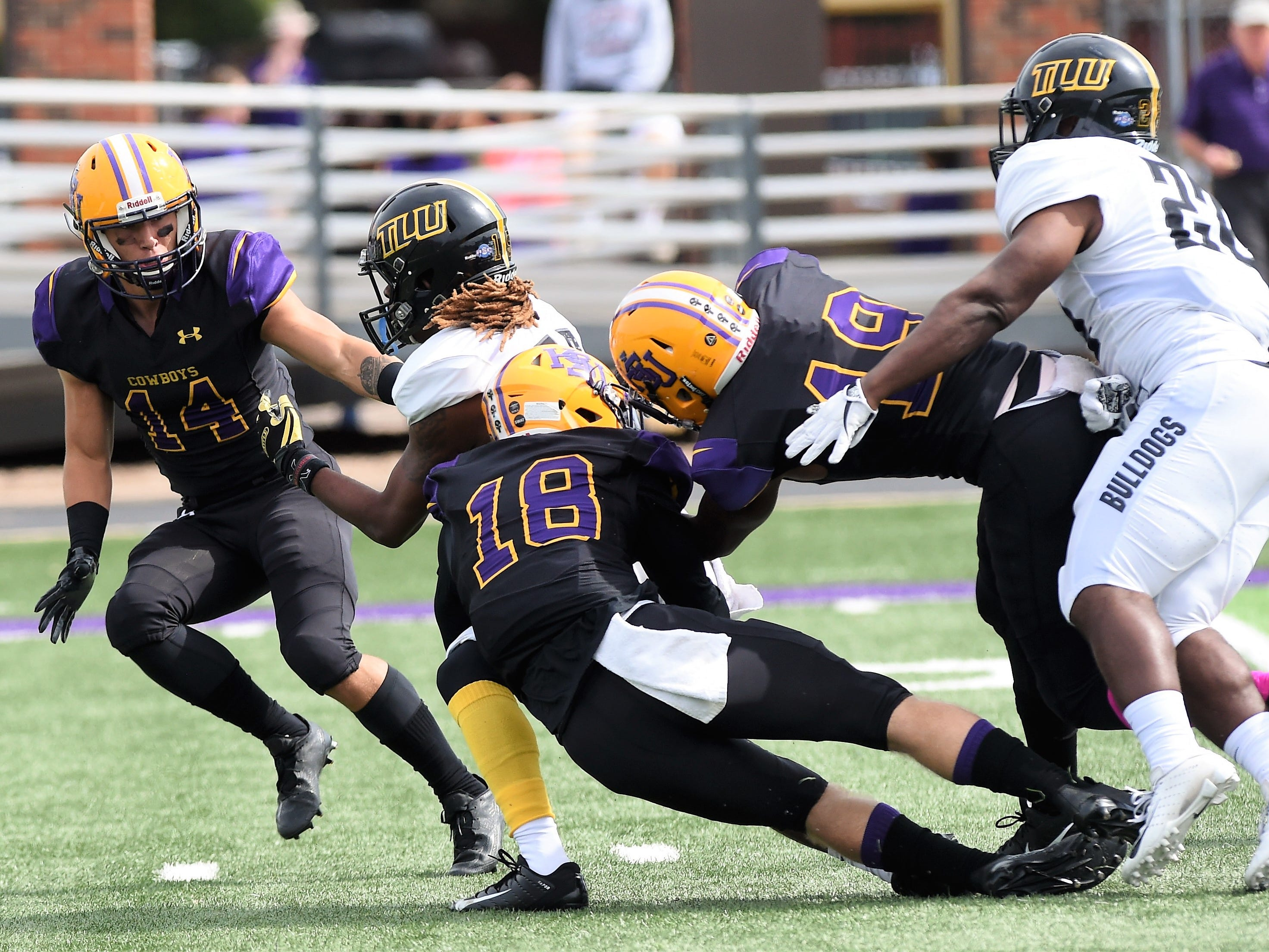 Hardin-Simmons' Travis Wilde (18) and Kelton McGee (19) make a special teams tackle against Texas Lutheran at Shelton Stadium on Saturday, Oct. 20, 2018.
