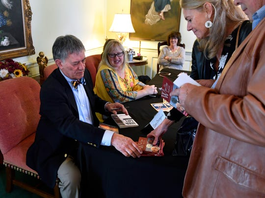 Glenn Dromgoole autographs books after the Boots & Books Luncheon Saturday at the Abilene Woman's Club.