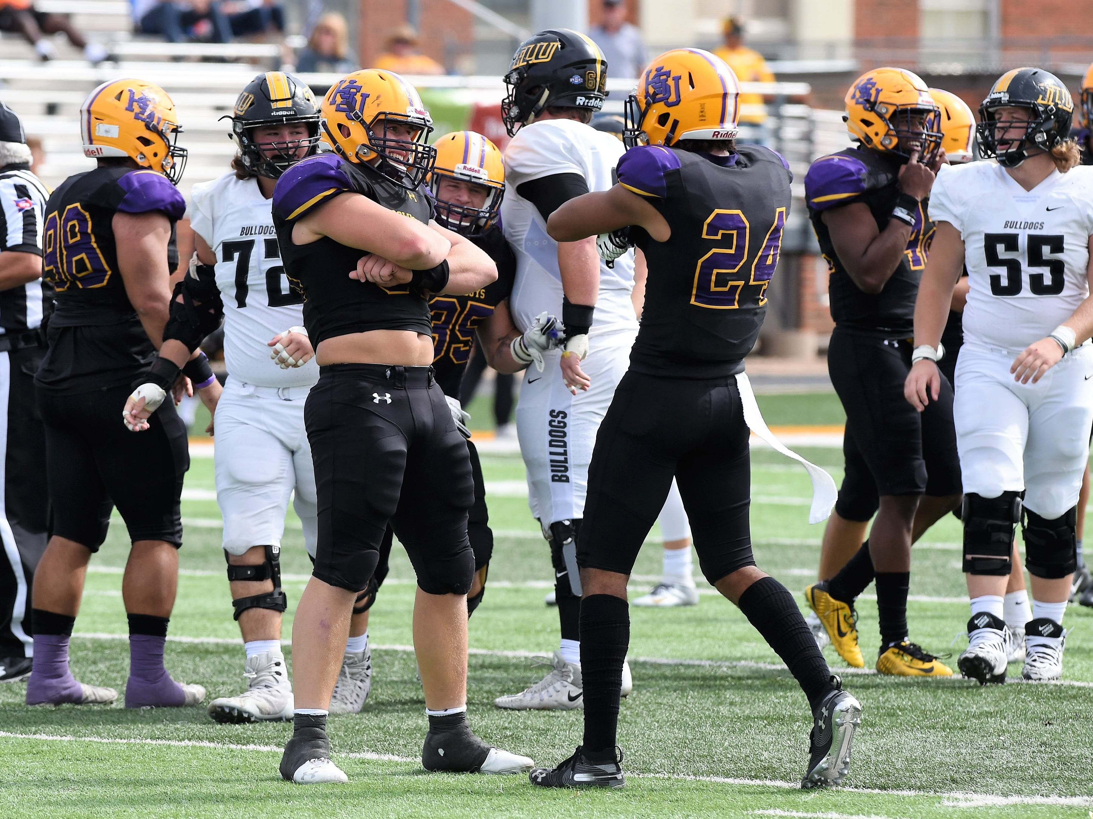 Hardin-Simmons' Hunter Creasey (96) and Dedrick Strambler (24) celebrate after a sack against Texas Lutheran at Shelton Stadium on Saturday, Oct. 20, 2018.