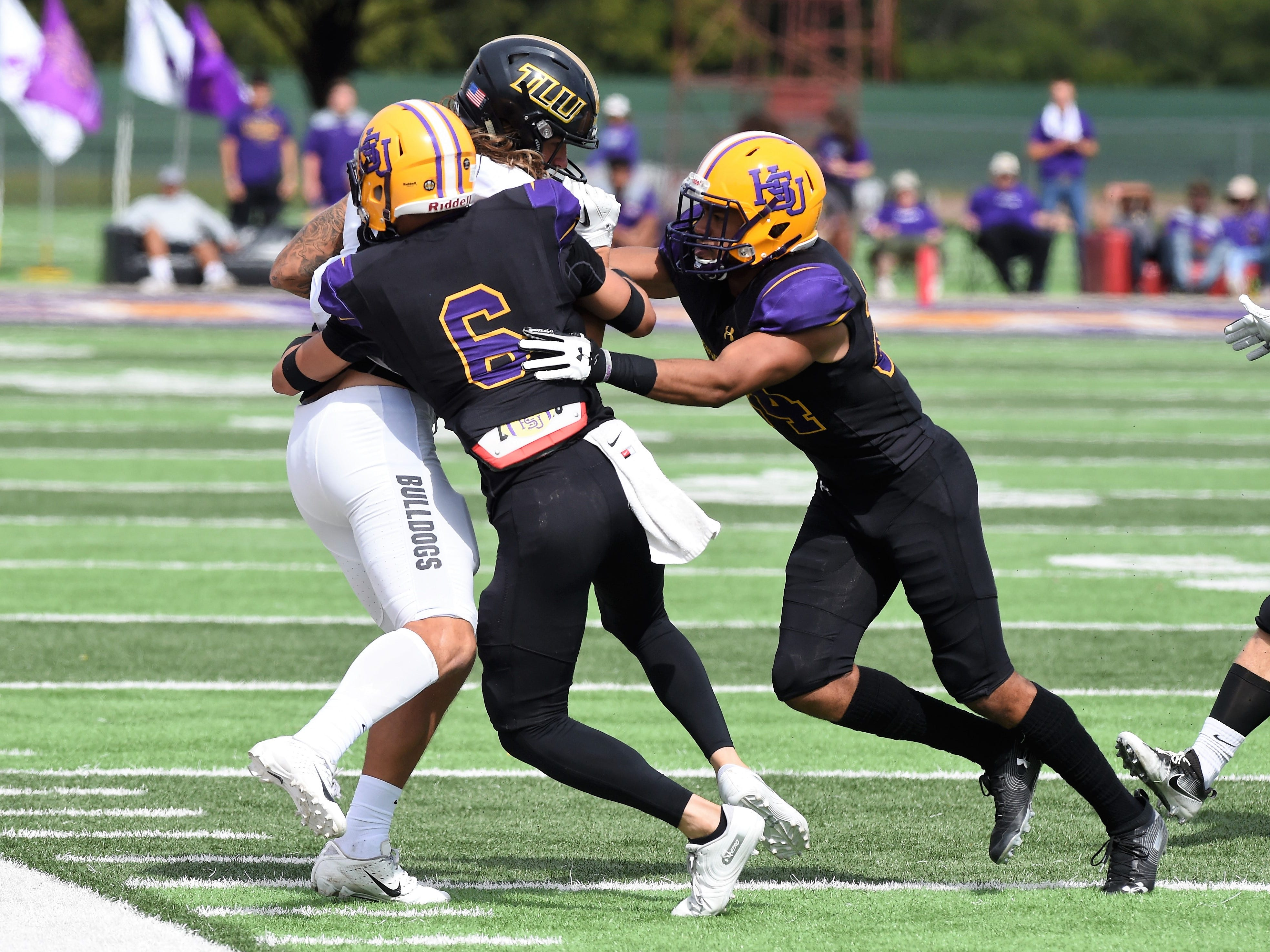 Hardin-Simmons defensive back Zac Richardson (6) and Dedrick Strambler (24) combine to make a tackle against Texas Lutheran at Shelton Stadium on Saturday, Oct. 20, 2018.