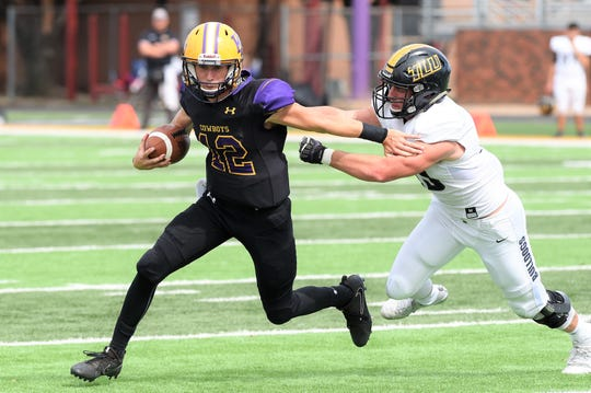 Hardin-Simmons quarterback Ty Hooper (12) tries to escape a Texas Lutheran defender at Shelton Stadium on Saturday, Oct. 20, 2018.