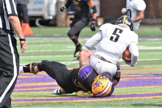 Hardin-Simmons linebacker Chris Miller (35) pulls down Texas Lutheran's Charles Robinson (5) at Shelton Stadium on Saturday, Oct. 20, 2018.