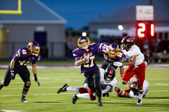 Wylie's Bailey Hicks (27) dodges a tackle by Wichita Falls High School's Baylen Faris and attempts to ward off defensive back Uriel Vigil during their game Friday at Bulldog Stadium. WFHS won, 64-22.