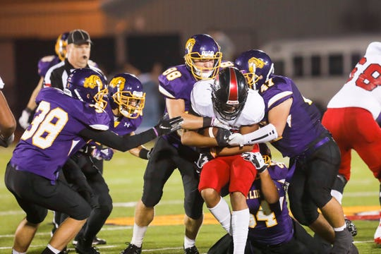 A pack of Wylie defenders, including Brodey Baker (88) and Dayton Barnes (47), takes down Wichita Falls High School's Isiah Cherry (10) Friday at Bulldog Stadium. WF won the homecoming game, 64-22.