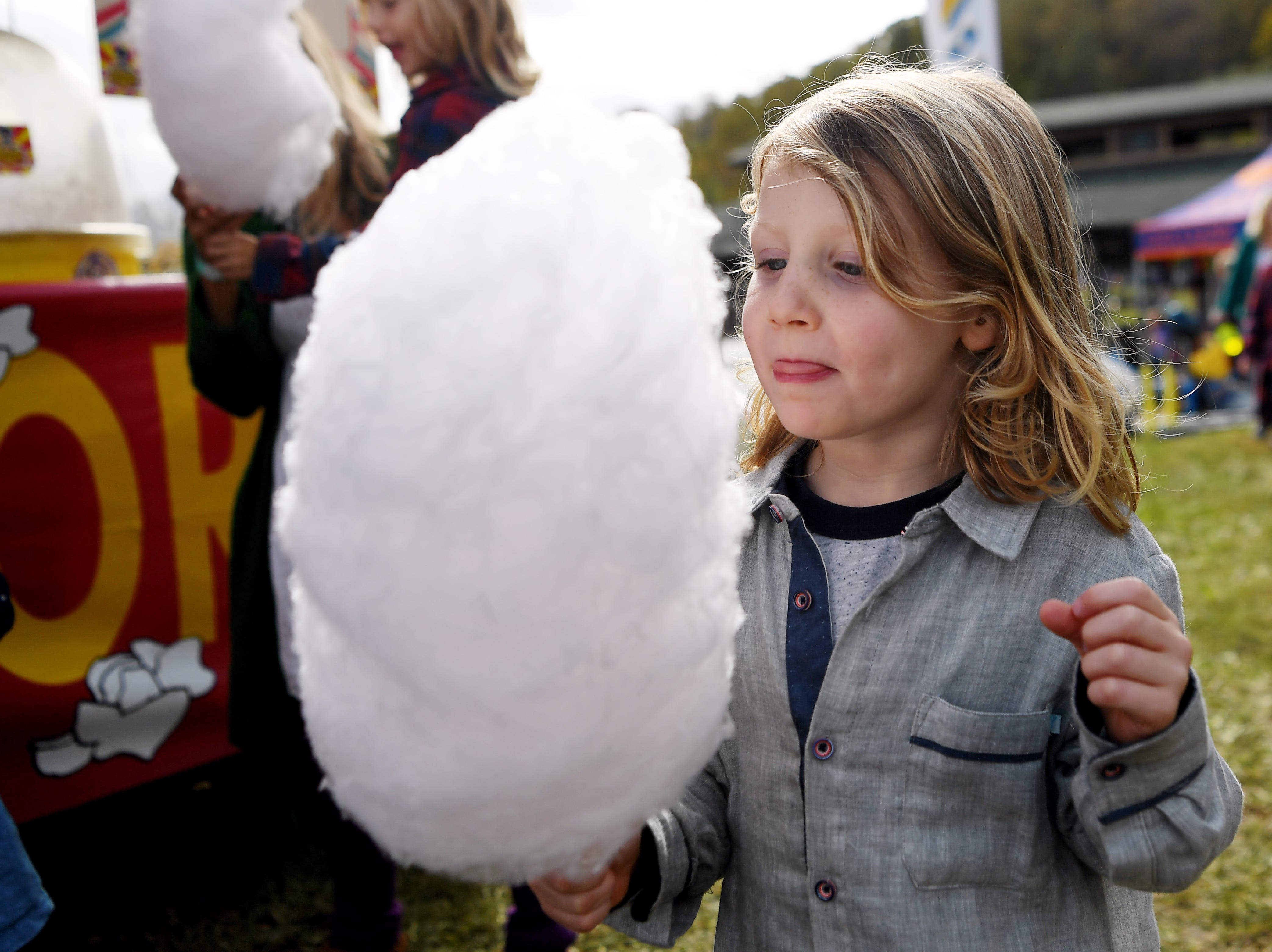 Foster Mitchell, 4, eats cotton candy at the Lake Eden Arts Festival in Black Mountain Oct. 20, 2018.