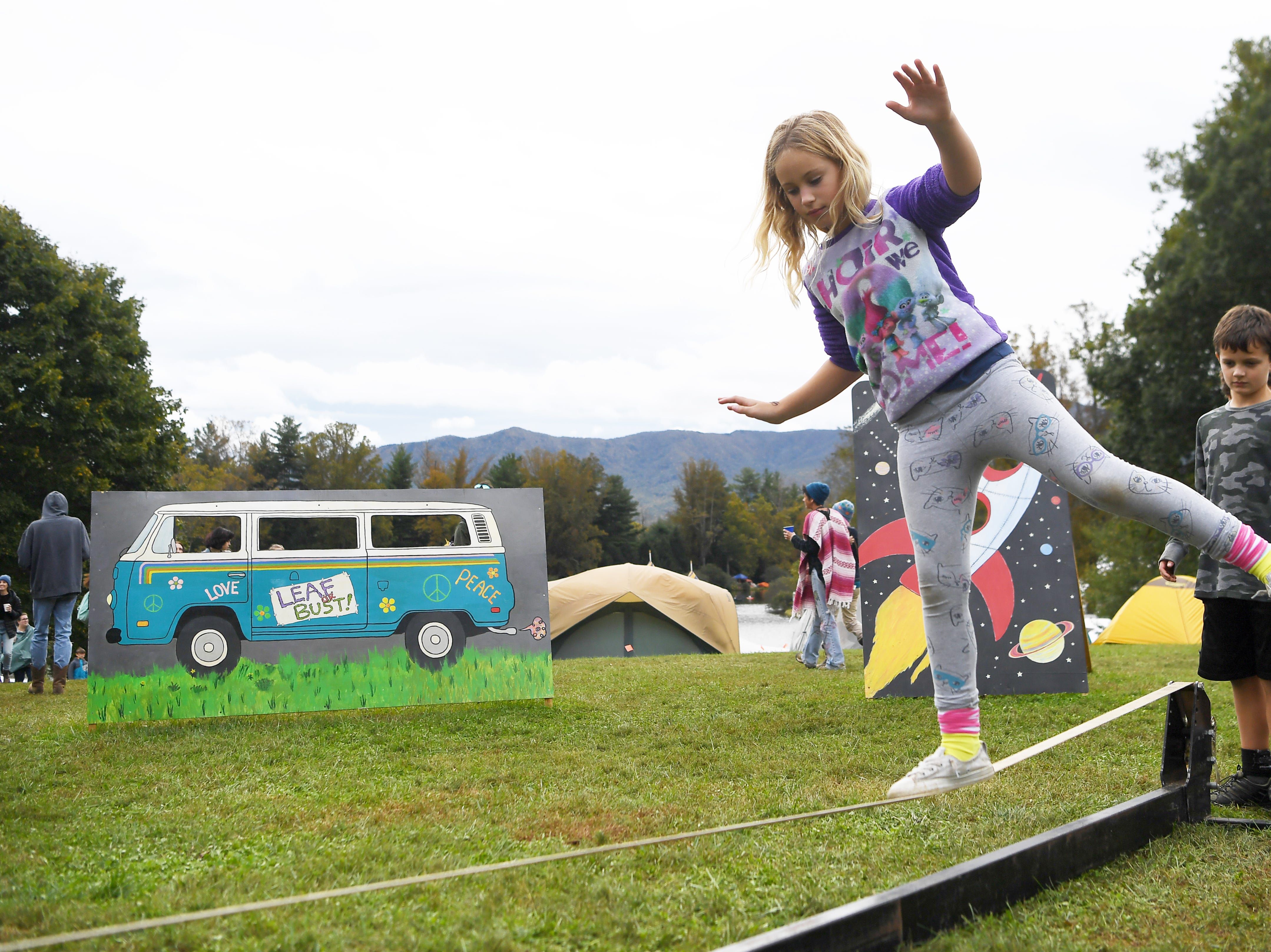 Miriam Creech, 9, tests her balance on a slack line at the 47th LEAF Festival at Lake Eden in Black Mountain Oct. 20, 2018.