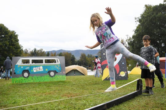 Miriam Creech tests her balance on a slack line at the 47th LEAF Festival in October at Lake Eden in Black Mountain. LEAF returns in May.